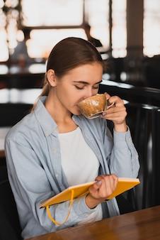 Mulher linda tomando café e segurando um caderno