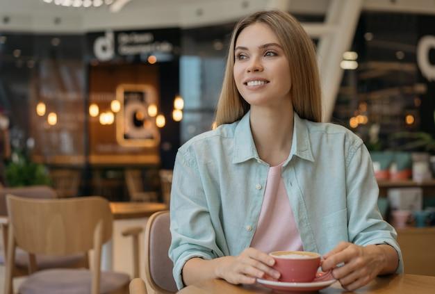 Mulher linda tomando café em um café