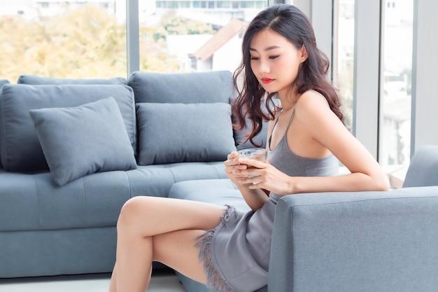 Mulher linda tomando café na sala de estar.