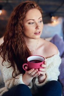 Mulher linda tomando chá quente em dia de inverno