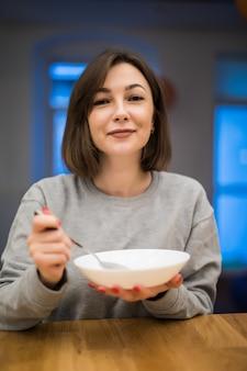 Mulher linda tomando seu café da manhã em sua cozinha