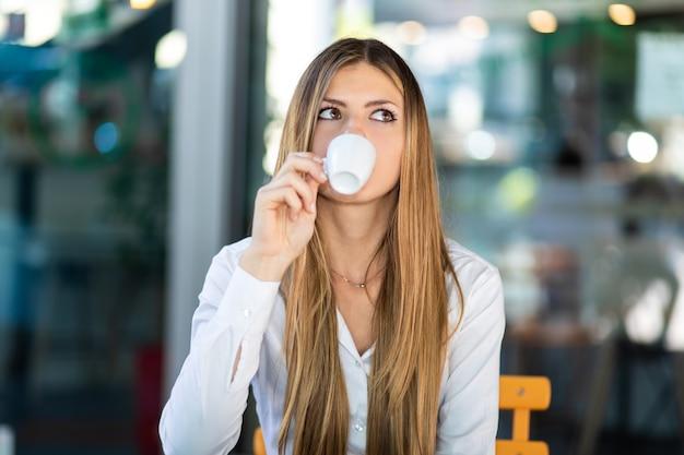 Mulher linda tomando um café em um café
