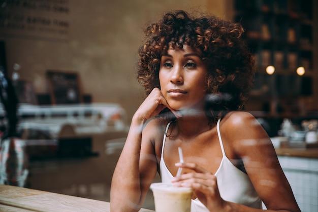 Mulher linda tomando uma bebida dentro de um café, vista através da tela Foto Premium