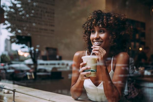 Mulher linda tomando uma bebida dentro de um café, vista através da tela