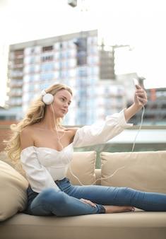 Mulher linda tomando uma selfie enquanto ouve a música