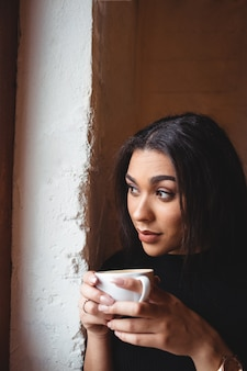 Mulher linda tomando uma xícara de café no café
