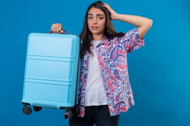 Mulher linda turista em pé com uma mala de viagem, parecendo confusa com a mão na cabeça por engano, lembre-se do erro, esqueci o conceito de memória ruim sobre o espaço azul isolado