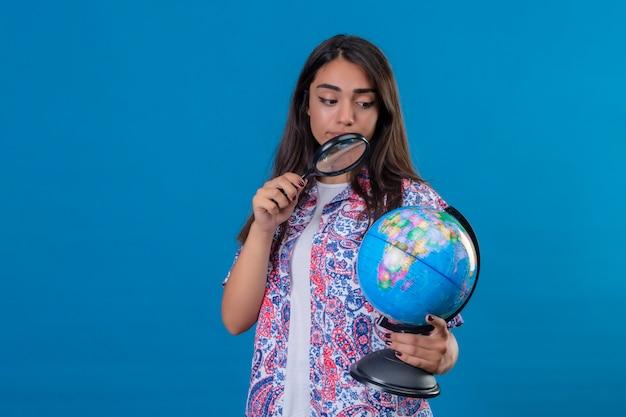 Mulher linda turista segurando e olhando através de uma lupa no globo com interesse em pé sobre o espaço azul