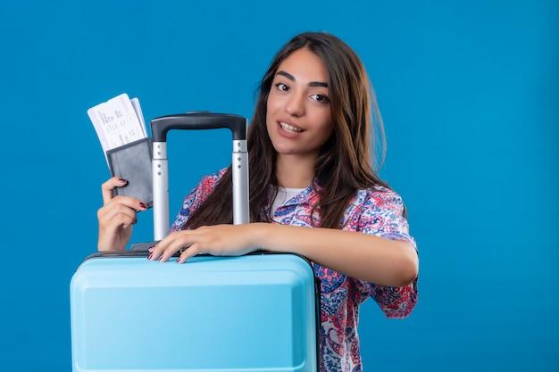 Mulher linda turista segurando uma mala de viagem e passaporte com bilhetes com um sorriso no rosto conceito de viagem feliz e positivo em pé sobre o espaço azul