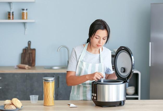 Mulher linda usando fogão elétrico em casa