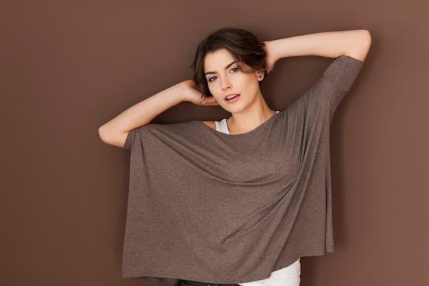 Mulher linda usando uma blusa grande e posando na parede marrom