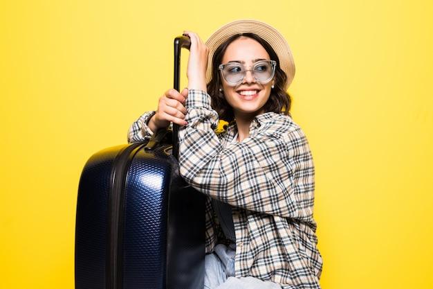 Mulher linda viajante e bagagem isolada na parede amarela, verão, conceito de viagens.