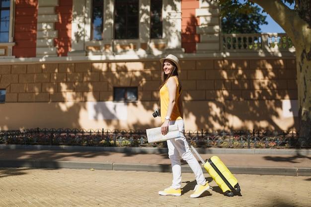 Mulher linda viajante turista no chapéu de roupas casuais de verão amarelo com mapa da cidade mala andar na cidade ao ar livre. garota viajando para o exterior para viajar no fim de semana. conceito de estilo de vida de viagem de turismo.