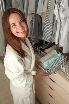 Mulher lindamente colocar as coisas em recipientes. armazenamento de roupas.
