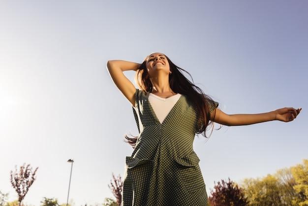 Mulher livre e feliz curtindo a natureza. menina de beleza ao ar livre. conceito de liberdade. menina de beleza sobre o céu e o sol. raios de sol. prazer.