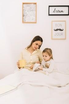Mulher, livro leitura, com, filha, em, manhã