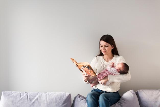 Mulher, livro leitura, e, segurando criança