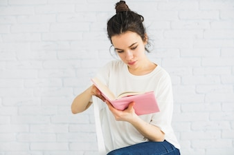 Mulher, livro leitura, perto, parede branca