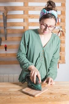 Mulher lixar uma madeira restaurada