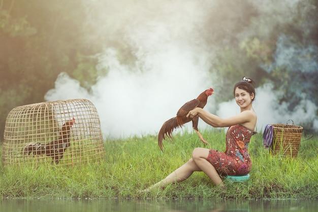 Mulher local asiática com galo lutando, tailândia