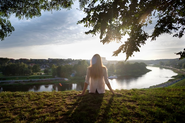 Mulher localização na grama, relaxando e apreciando a vista do rio