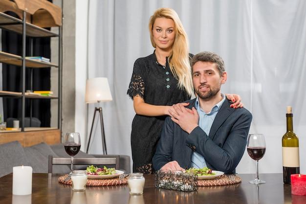 Mulher loira abraçando o homem na mesa com pratos e copos