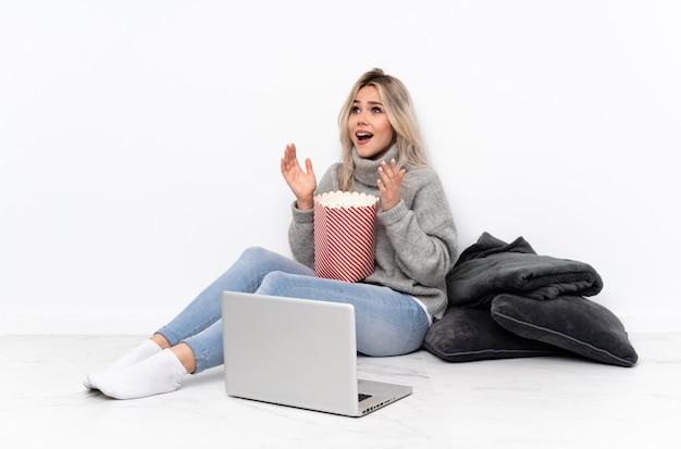 Mulher loira adolescente comendo pipoca enquanto assiste a um filme no laptop com expressão facial de surpresa