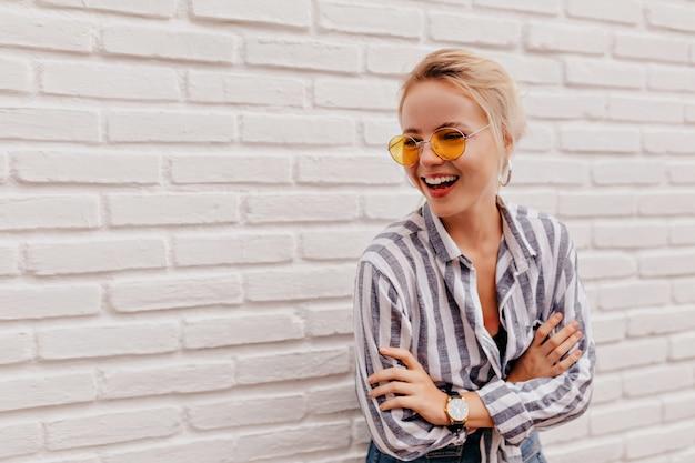 Mulher loira adorável feliz usando óculos laranja elegantes em uma camisa listrada e posando com um sorriso adorável