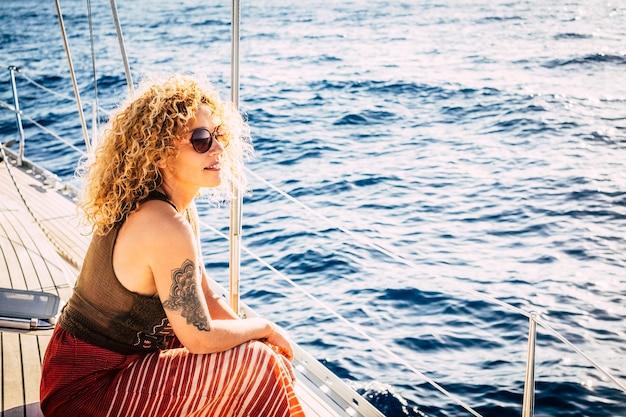 Mulher loira adulta jovem e atraente sorria e aproveita a excursão sentado no convés do barco à vela, olhando o mar azul ao redor