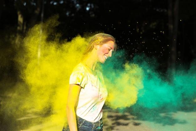 Mulher loira alegre brincando com tinta seca amarela e verde holi no parque