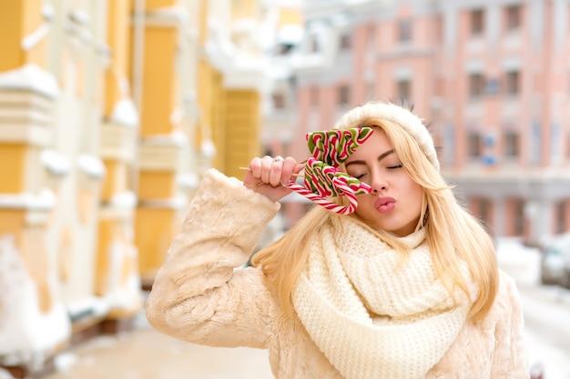 Mulher loira alegre com cabelo comprido, usando um chapéu de malha quentinho, segurando deliciosos doces de natal