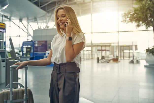 Mulher loira alegre com um sorriso no rosto enquanto fala por telefone