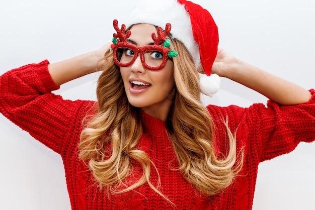 Mulher loira alegre e despreocupada com óculos de baile de máscaras fofos e chapéu de ano novo em suéter de malha vermelha posando