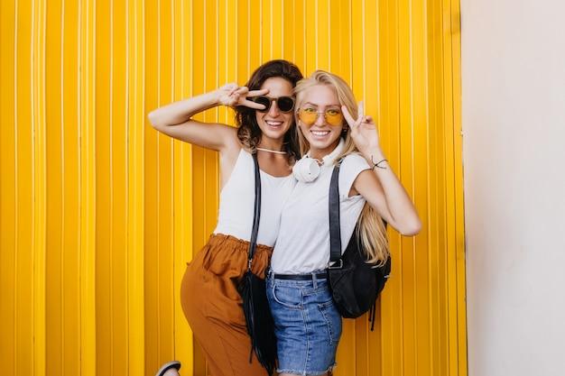 Mulher loira alegre em óculos de sol amarelos, brincando com a melhor amiga.