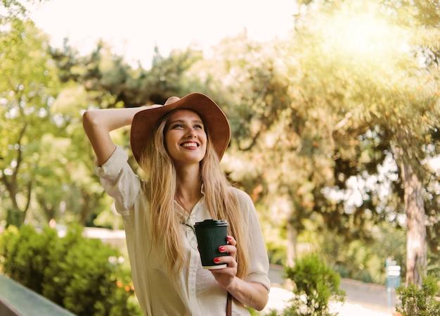 Mulher loira alegre em roupas de estilo casual e chapéu de feltro, bebendo café em qualquer lugar e caminhando pela cidade