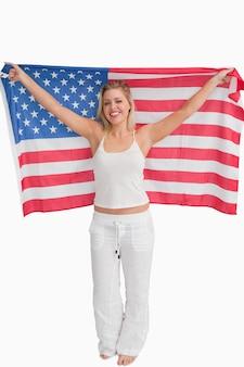 Mulher loira alegre levantando a bandeira americana