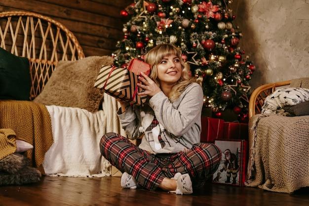 Mulher loira alegre nas decorações de ano novo. época de natal. feliz feriado. arvore de natal. presente surpresa de ano novo