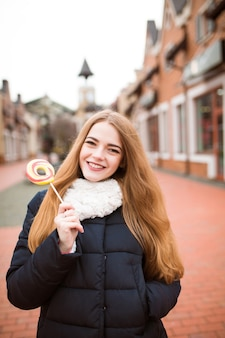 Mulher loira alegre se divertindo com um pirulito colorido no fundo da rua desfocada