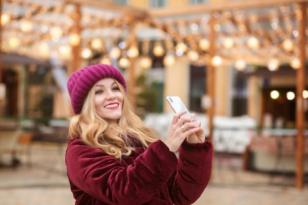 Mulher loira alegre tirando uma selfie no celular ao fundo das luzes de natal