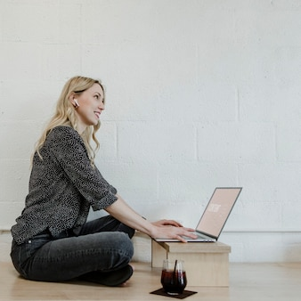 Mulher loira alegre usando um laptop em um piso de madeira