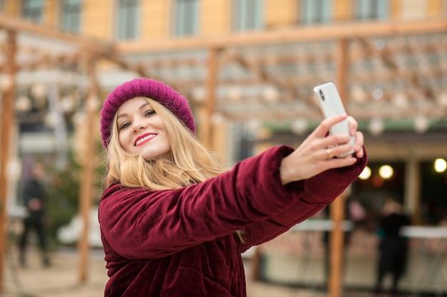 Mulher loira alegre vestida com roupas quentes fazendo selfie no fundo de uma guirlanda em kiev