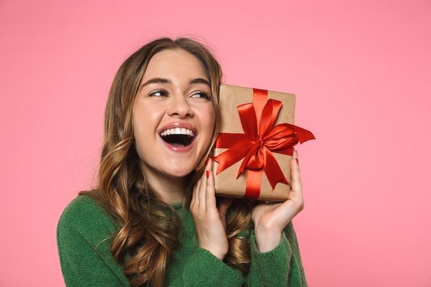Mulher loira alegre, vestindo um suéter verde segurando uma caixa de presente e olhando para longe por cima da parede rosa