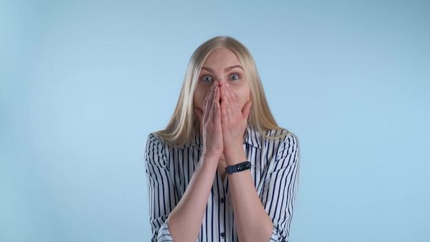 Mulher loira amplamente abrindo a boca em espanto