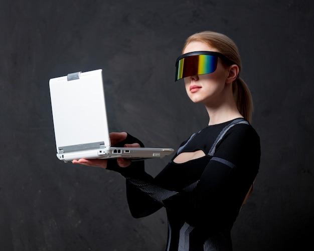 Mulher loira andróide em óculos vr e laptop em fundo escuro.