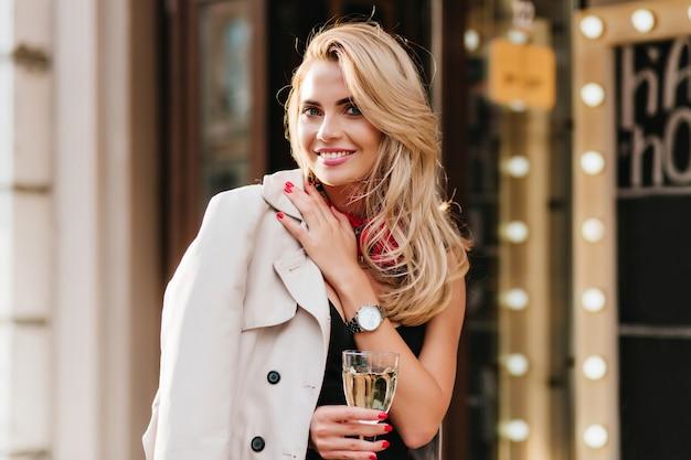 Mulher loira animada em um relógio de pulso de prata na moda, posando com prazer no aniversário dela, segurando um copo de vinho. menina encantadora com pele bronzeada, bebendo champanhe e se divertindo no fim de semana.