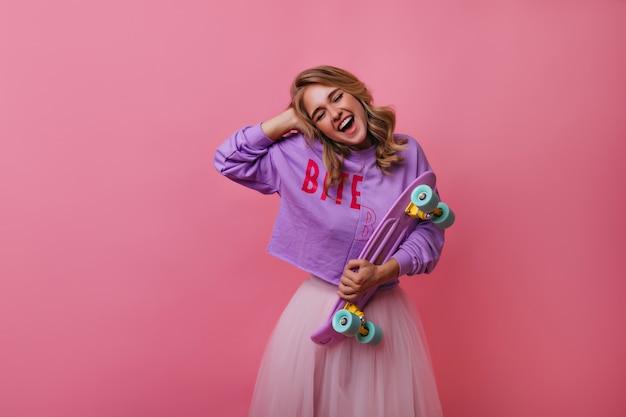 Mulher loira animada rindo com os olhos fechados enquanto posava com o skate. garota encaracolada despreocupada em pé de camisa roxa rosa.
