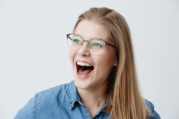 Mulher loira animada usando óculos, camisa jeans, exclama alegremente, feliz em saber sobre a inscrição na universidade, os sonhos de se tornar estudante por muito tempo, não pode acreditar no sucesso.