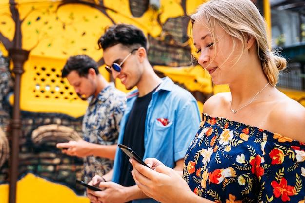 Mulher loira ao lado de dois jovens de diferentes etnias usando um celular no meio de uma rua com fachadas coloridas e arte de rua