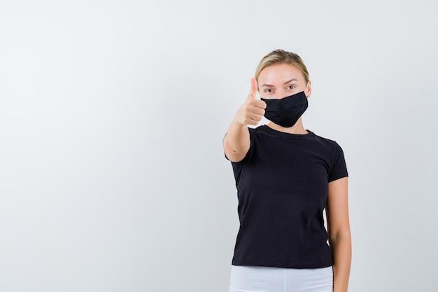 Mulher loira aparecendo com o polegar em camiseta preta, calça branca