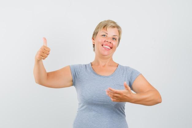 Mulher loira aparecendo os polegares e fingindo estar segurando algo na mão em uma camiseta azul clara e parecendo feliz. vista frontal.